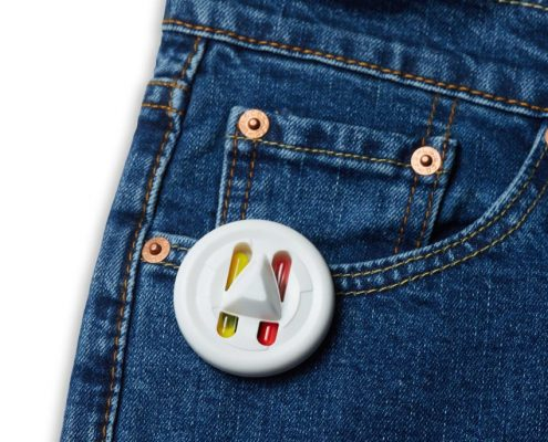 White circular security tag with ink attached to the pocket seam of a pair of jeans.