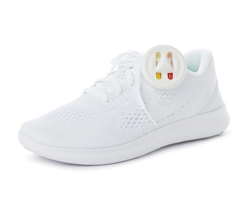 Small, white, circular security tag with ink attached to a white tennis shoe.