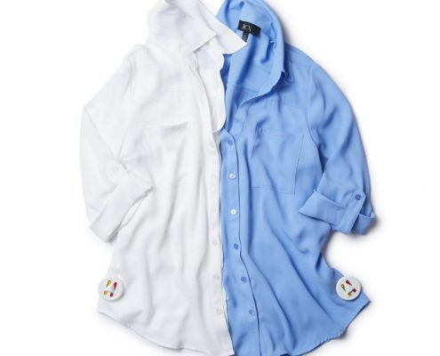 1 white and 1 blue men's button down dress shirts are both tagged with the small white security tag filled with ink.
