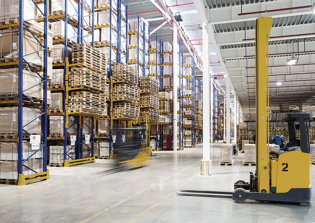 Forklifts drive in a 3PL warehouse to pick up palettes.