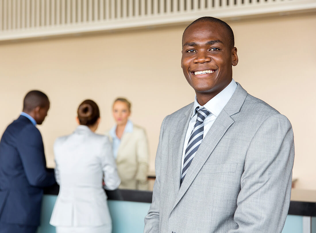 Bank representative smiles while a bank teller assists two customers with financial security at the counter.