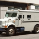 Side view of gray armored truck parked on street