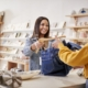 Female sales assistant in gift store serving female customer