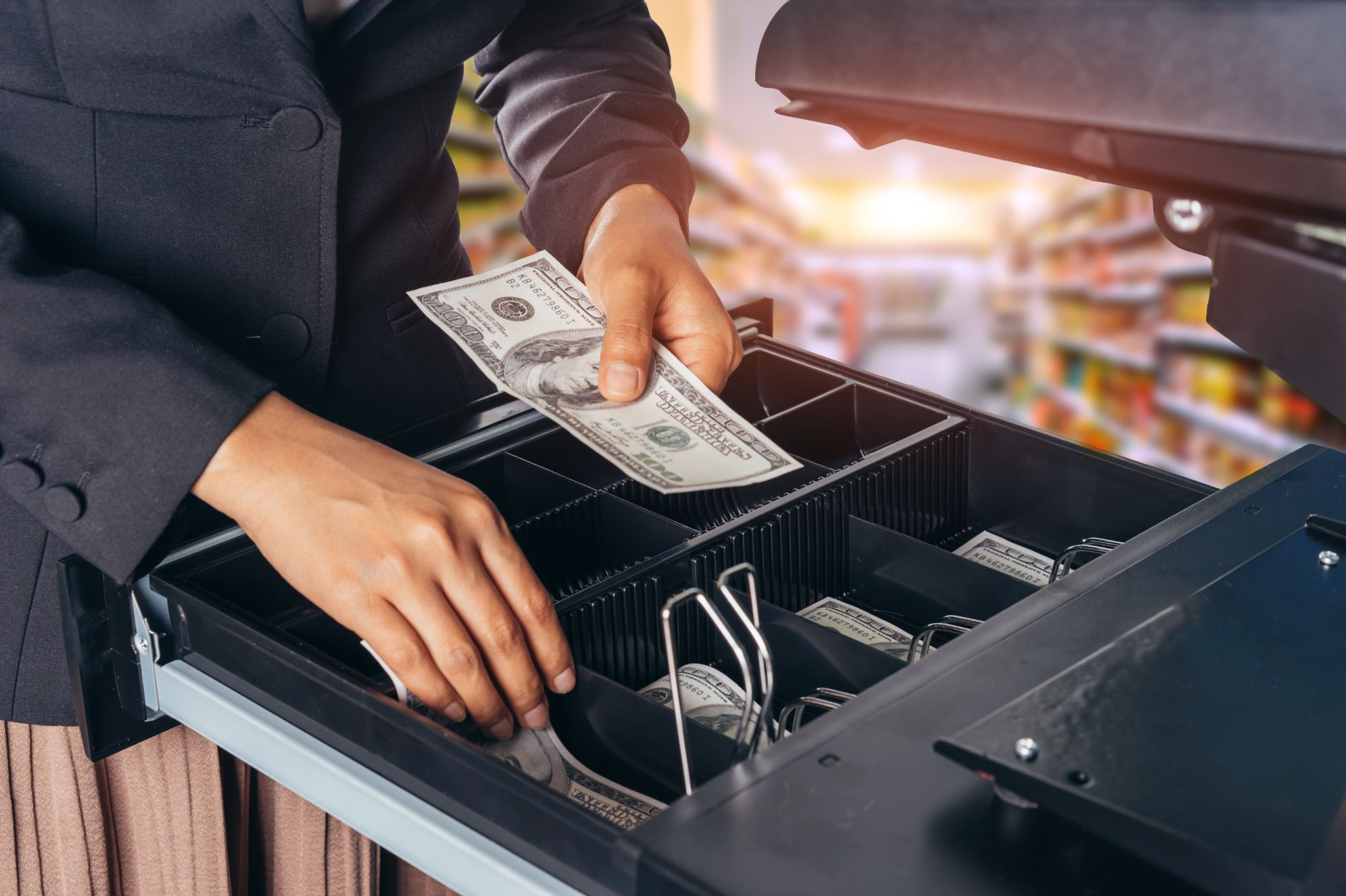 Female hand with money in supermarket shop