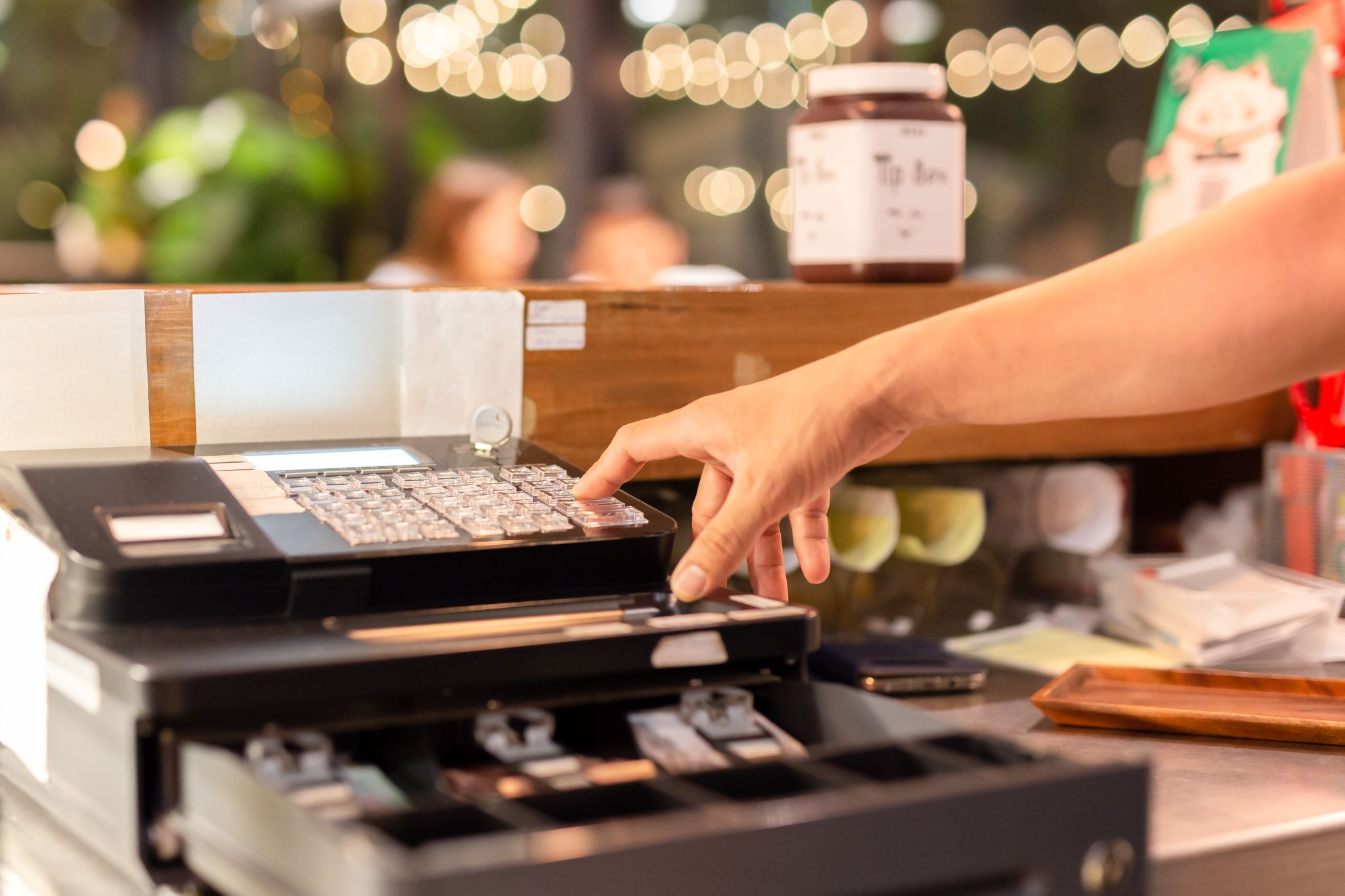Hand pressing electronic cash register in a shop