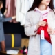 young woman is stealing red jeans in store