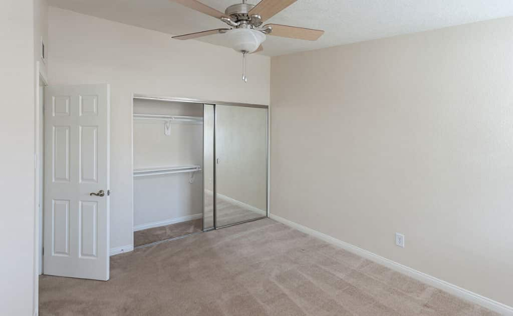 Empty carpeted bedroom with ceiling fan and closet