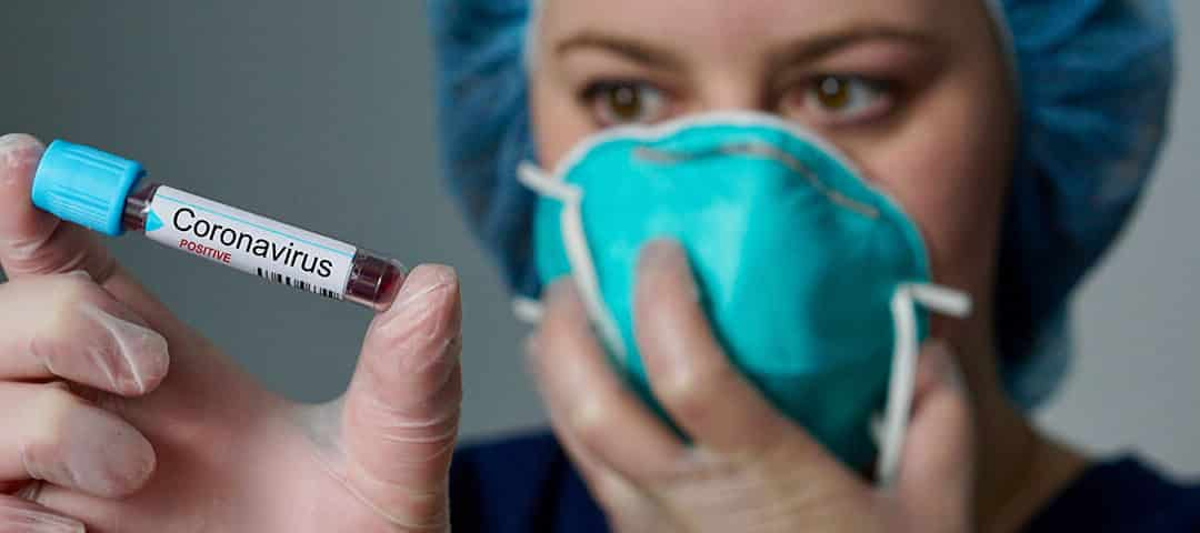 Doctor looking at a vial with coronavirus tag