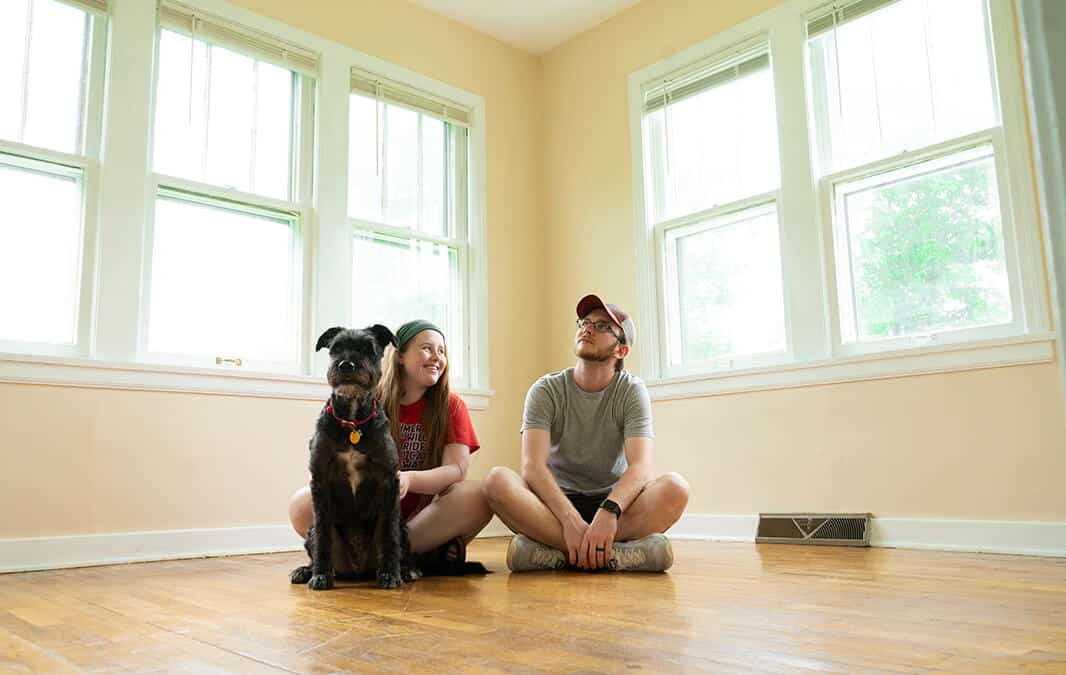 woman and man sitting in new home with dog