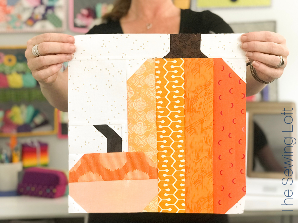 The patchwork construction of the Pretty Pumpkins quilt block makes it perfect for for quilters to play with their scraps.