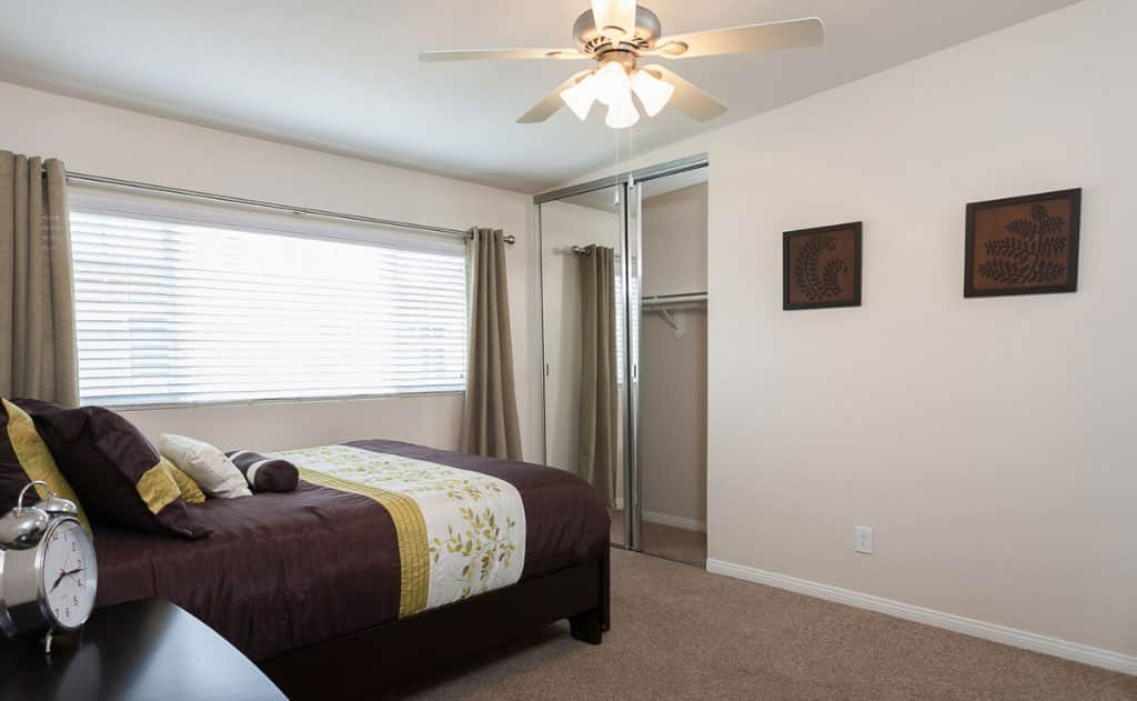Furnished bedroom with ceiling fan and carpet