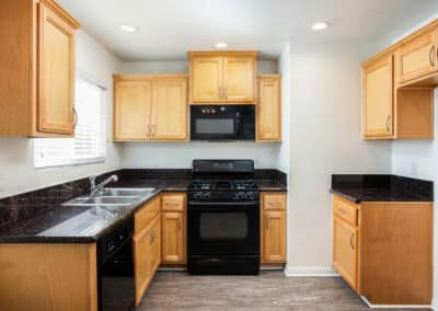 Galley kitchen with quartz counters, maple cabinets, and stainless steel appliances