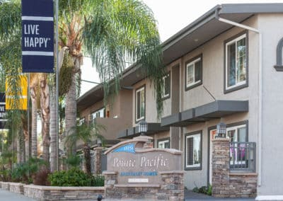 Exterior of Pointe Pacific apartments with trees and sign