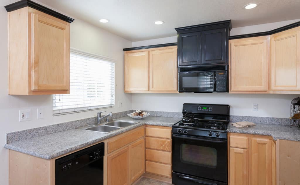 Kitchen with cabinets and dark countertops