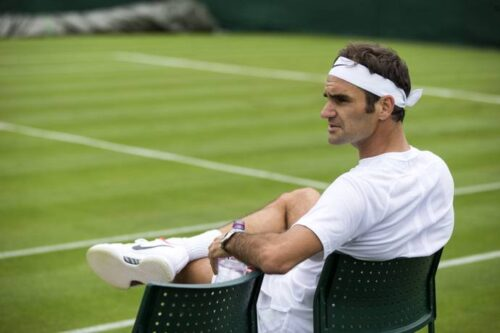 Roger Federer sitting on the sidelines of a grass tennis court