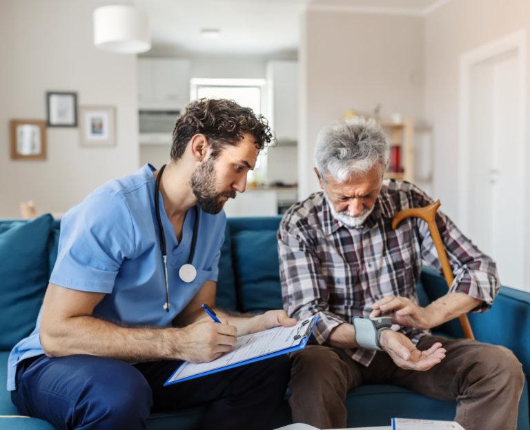 Senior Man Having Blood Pressure Checking by Male Caregiver in the Livingroom. Male Nurse Measuring Blood Pressure of Senior Patient at Home