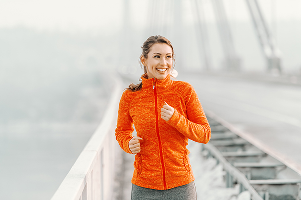 woman running across bridge after recovering from orthopedic spine surgery with dr. javier reto