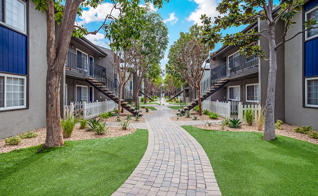 Garden pathway surrounded by apartment units and grass and trees