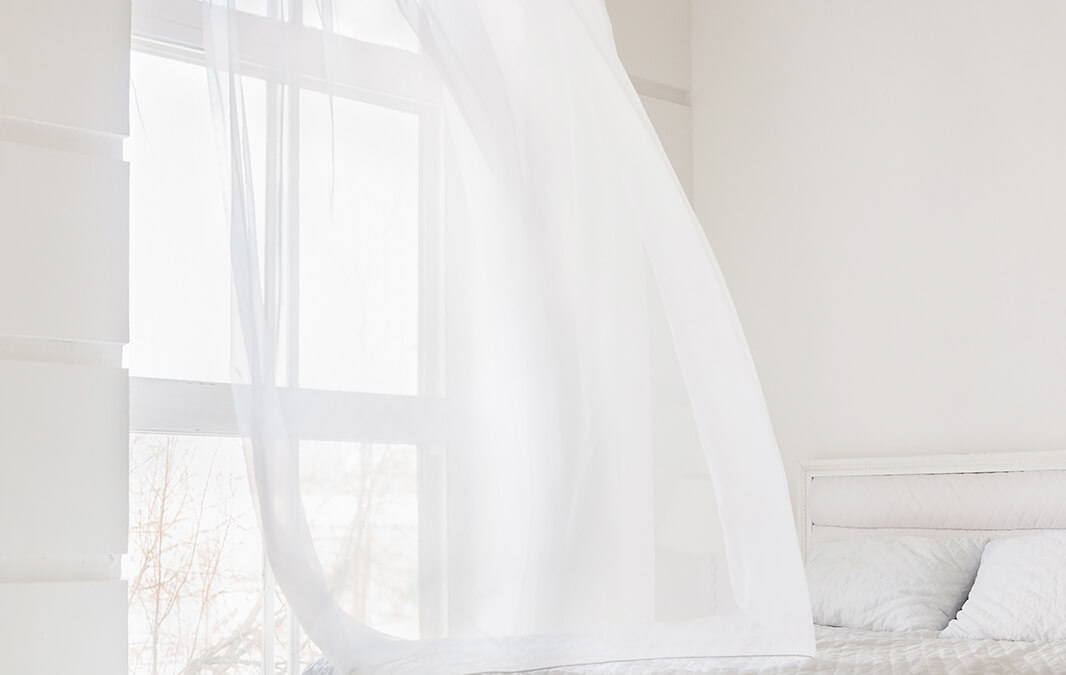 White curtain waving by the wind from the window