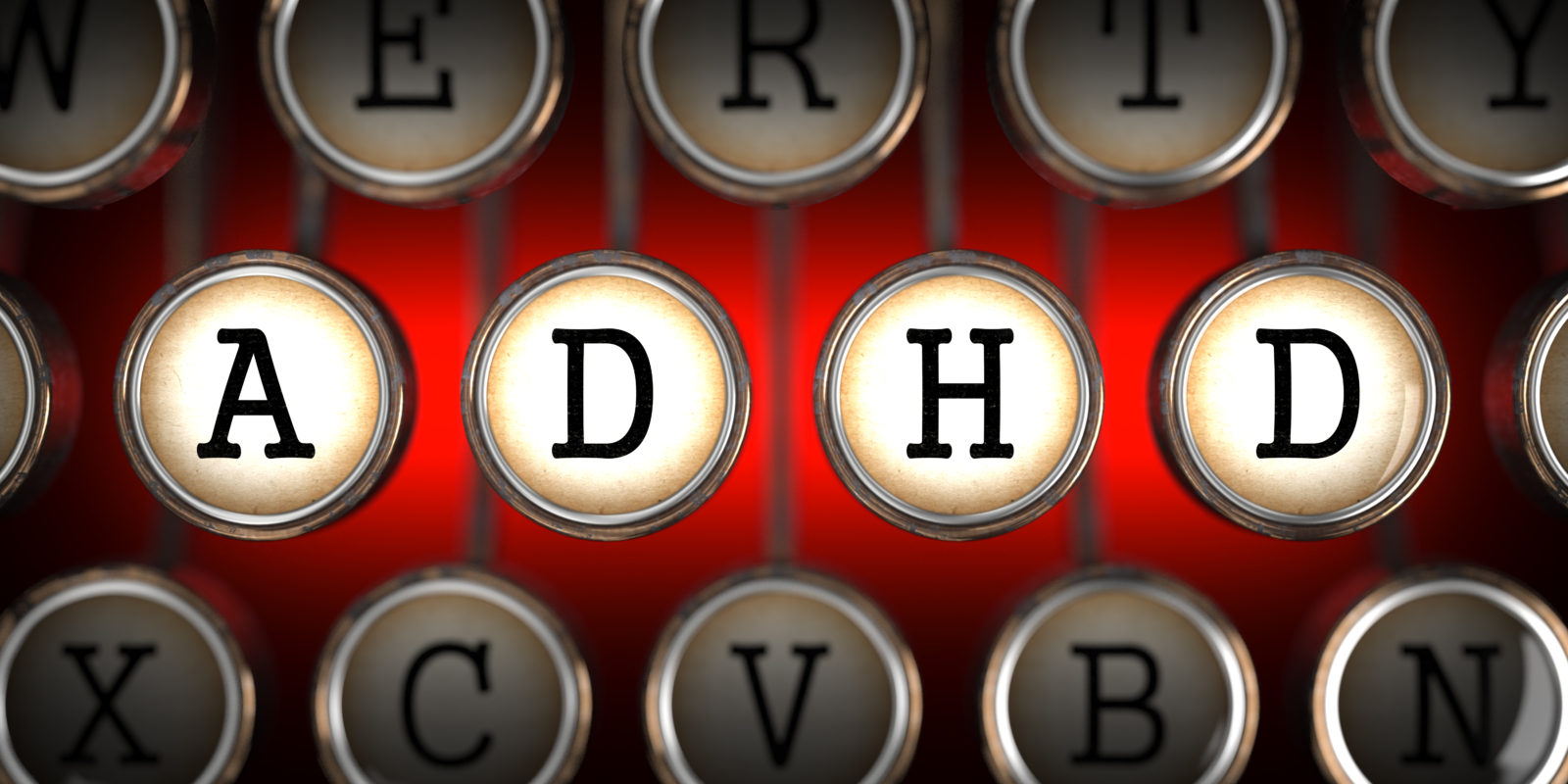 ADHD on Old Typewriter's Keys on Red Background.