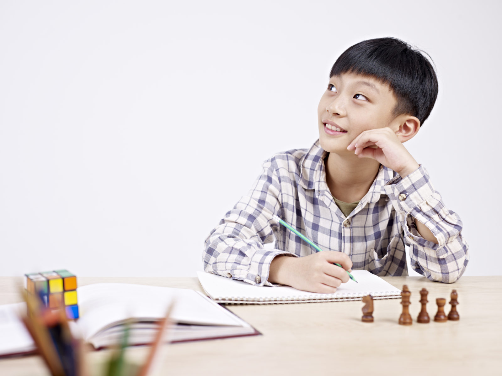 10 year-old asian elementary schoolboy looking away while studying.