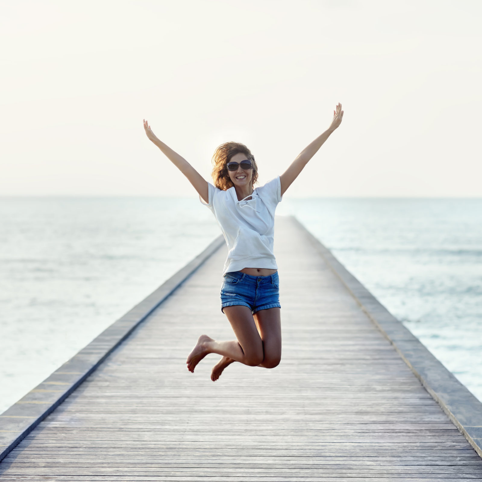 Happy jumping girl on the pier. Freedom concept