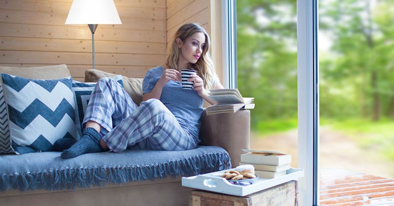 Woman enjoying a temperature controlled room after thermal low-e window film installation
