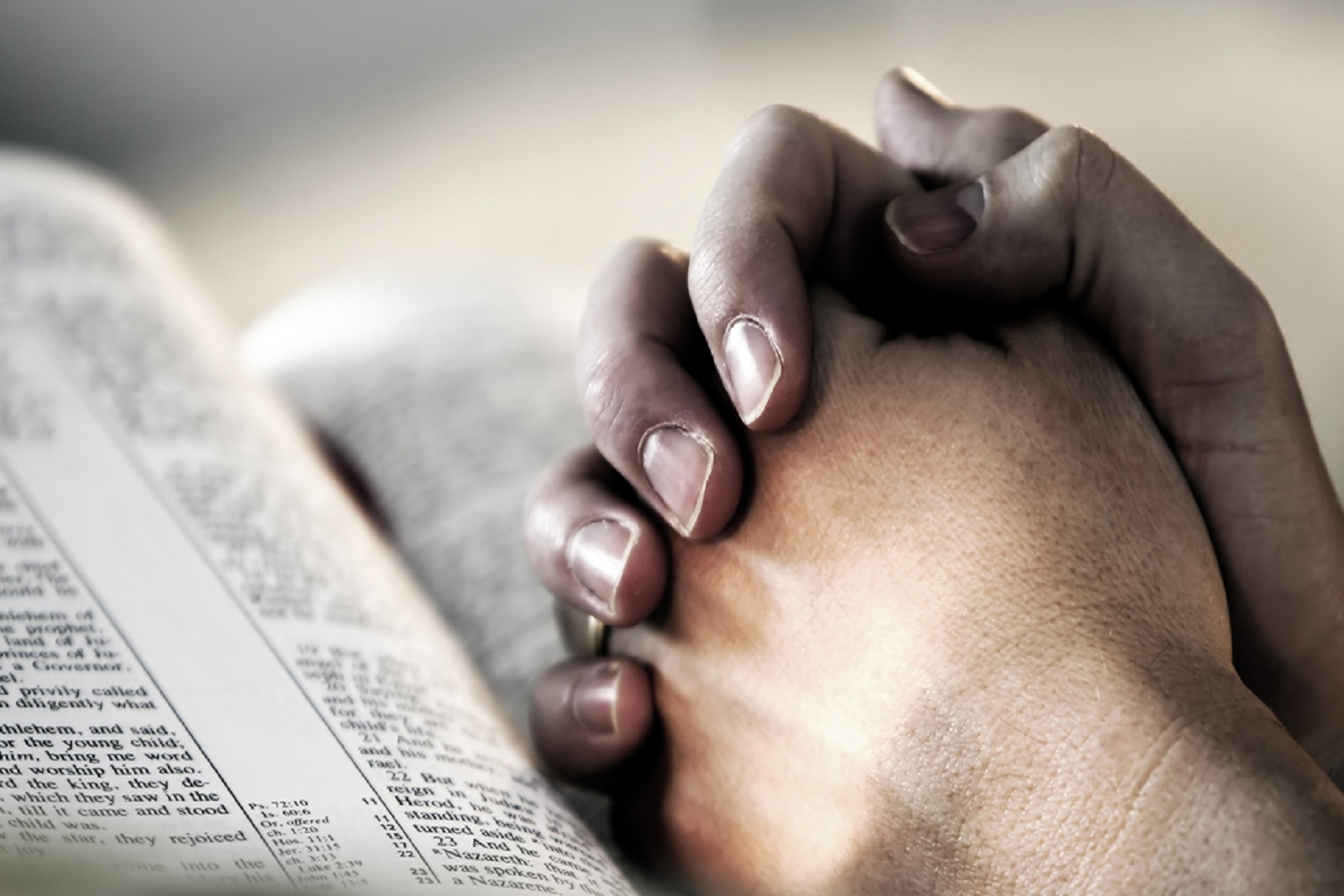 Man's hands folded in prayer over a Holy Bible - represents faith and spirtuality in everyday life.