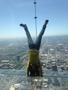 This photo is taken of a woman in SkyDeck as she faces Chicago's skyline upside down.