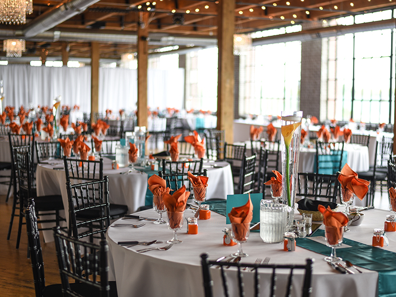 A photo of tables at a wedding reception with orange and turquoise decor.