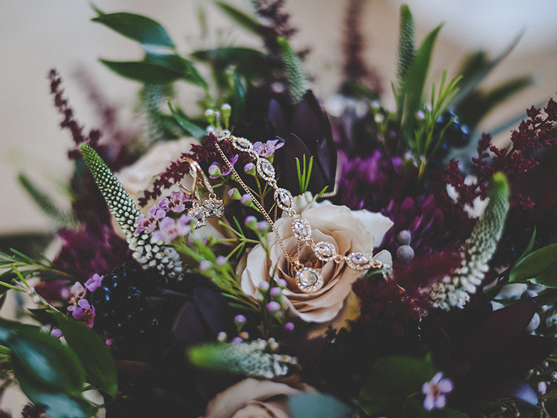 A photo of a gorgeous wedding bouquet with blush roses, deep purple mums and lush greenery accents