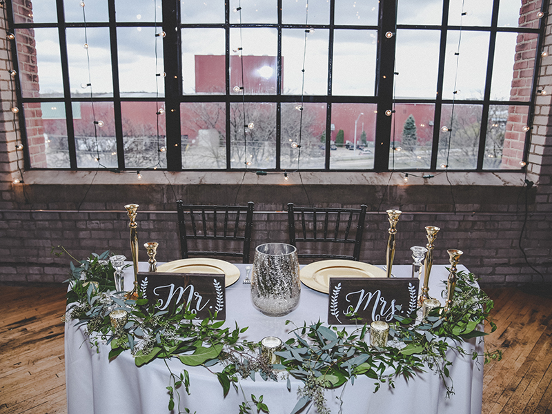 A photo of a wedding sweetheart table with greenery accents and gold candlesticks