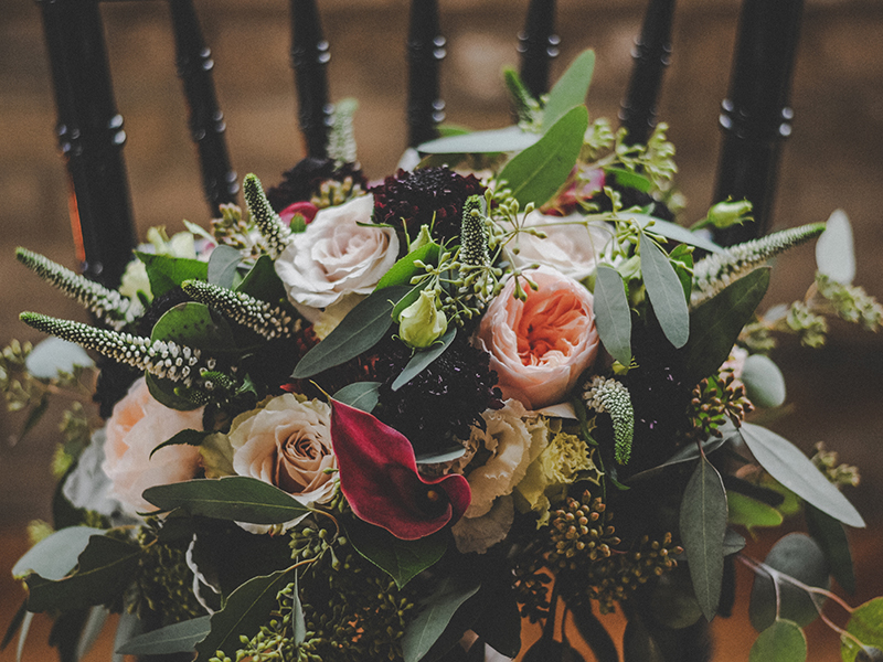 A photo of a rich wedding bouquet with peach and pink roses, lush greenery and purple accent flowers