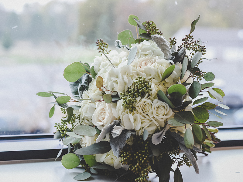 A photo of a romantic wedding bouquet with white roses, lush greenery and berry accents
