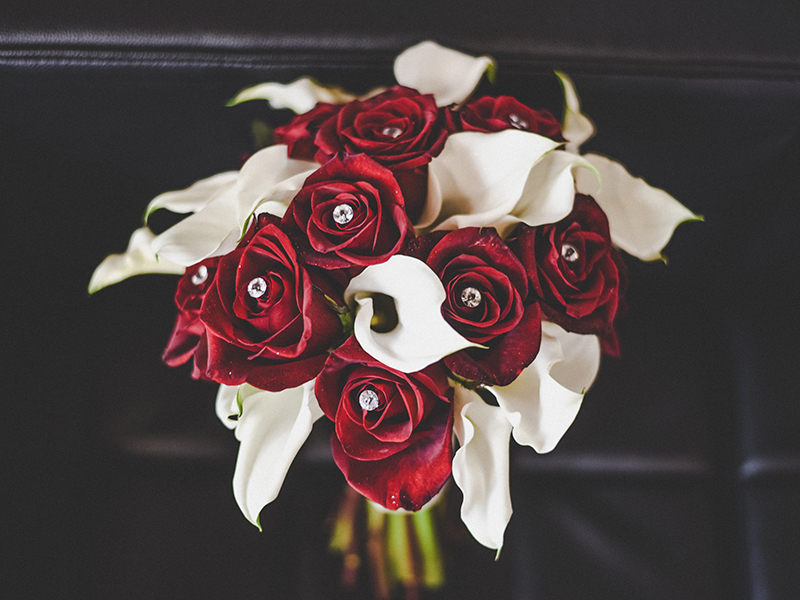 A photo of an elegant wedding bouquet with red roses, white calla lilies and diamond accents