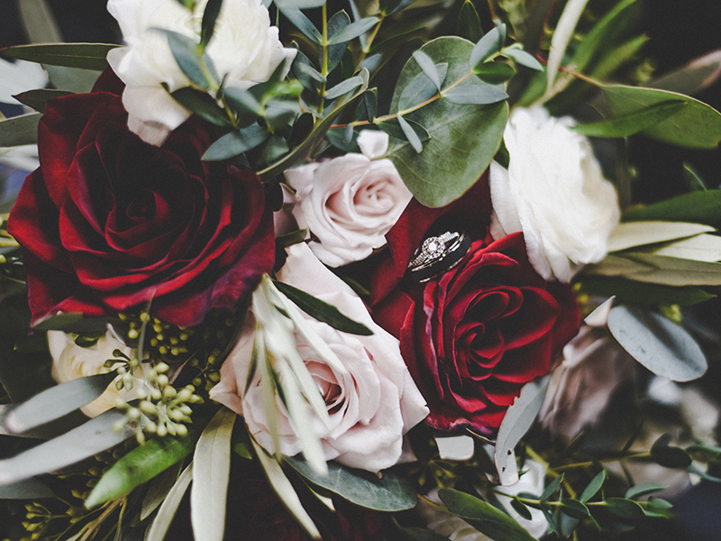 An organic wedding bouquet design with burgundy and pink roses and lush greenery