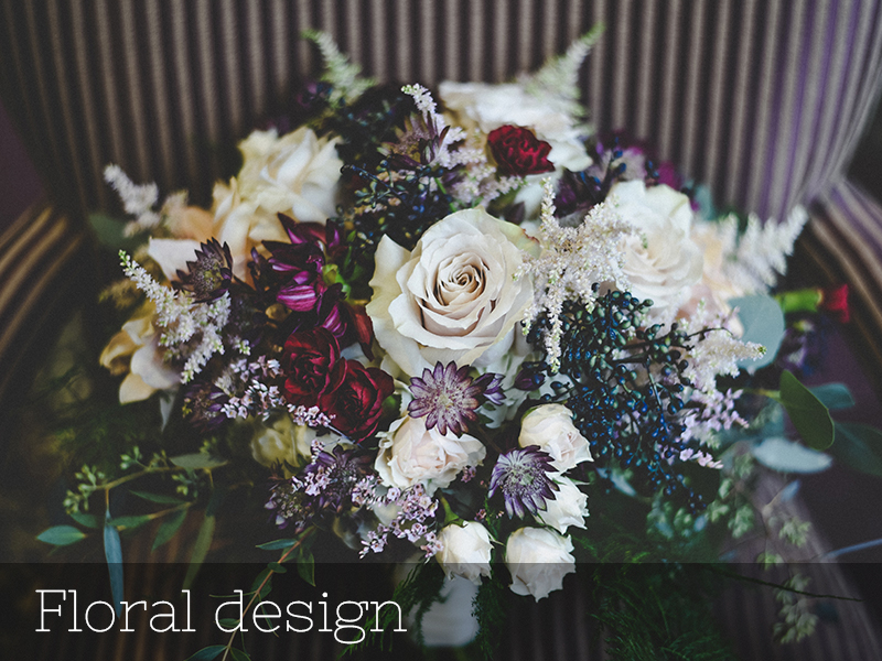 Photo of a wedding bouquet with white roses and purple flowers.