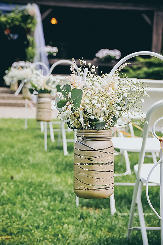 Summer wedding outdoor aisle decor. Gold painted mason jar with baby's breath