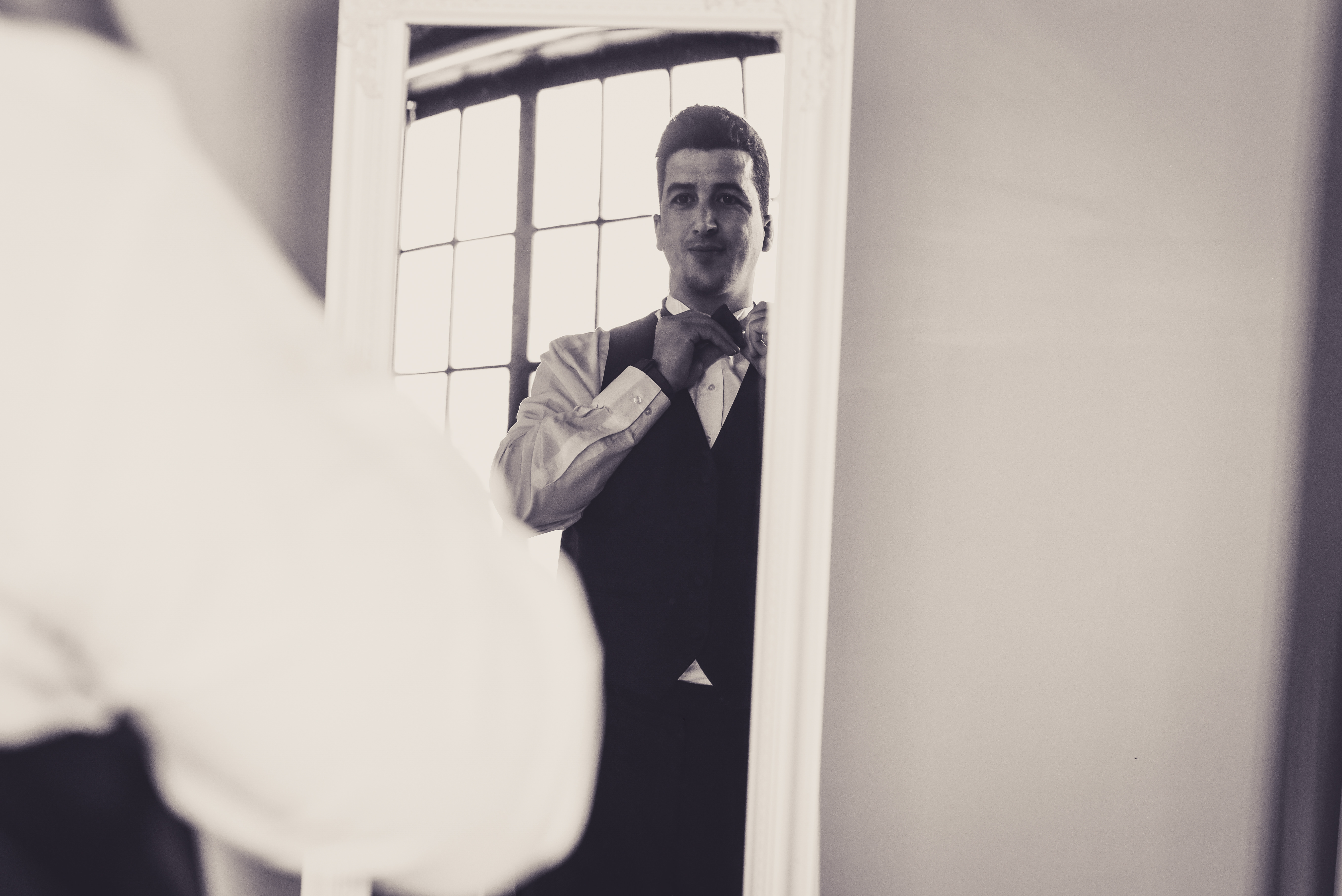 black and white photo of a groom adjusting his tie