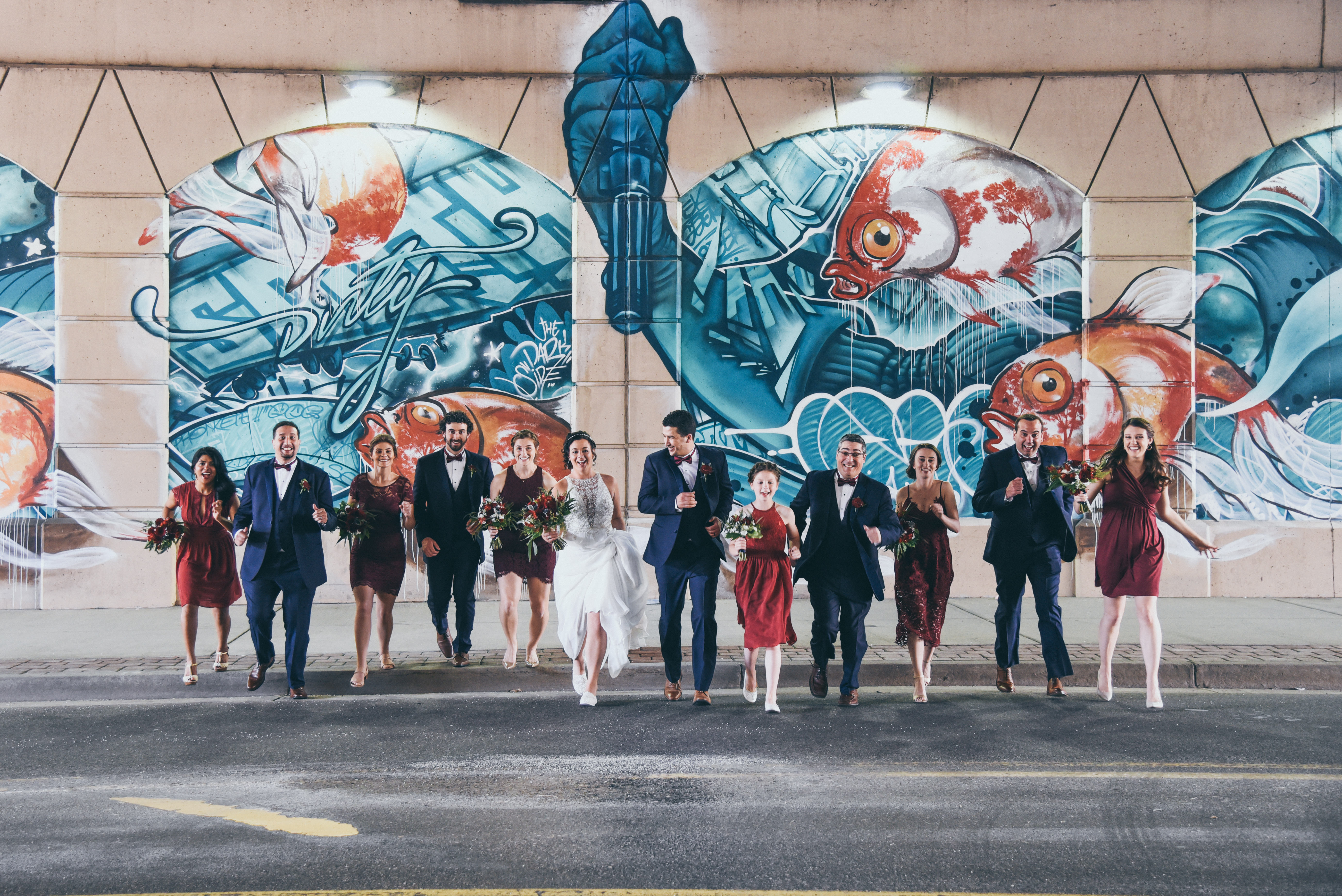 bride, groom, and bridal party running across the road together in front of a large underwater mural in grand rapids, michigan