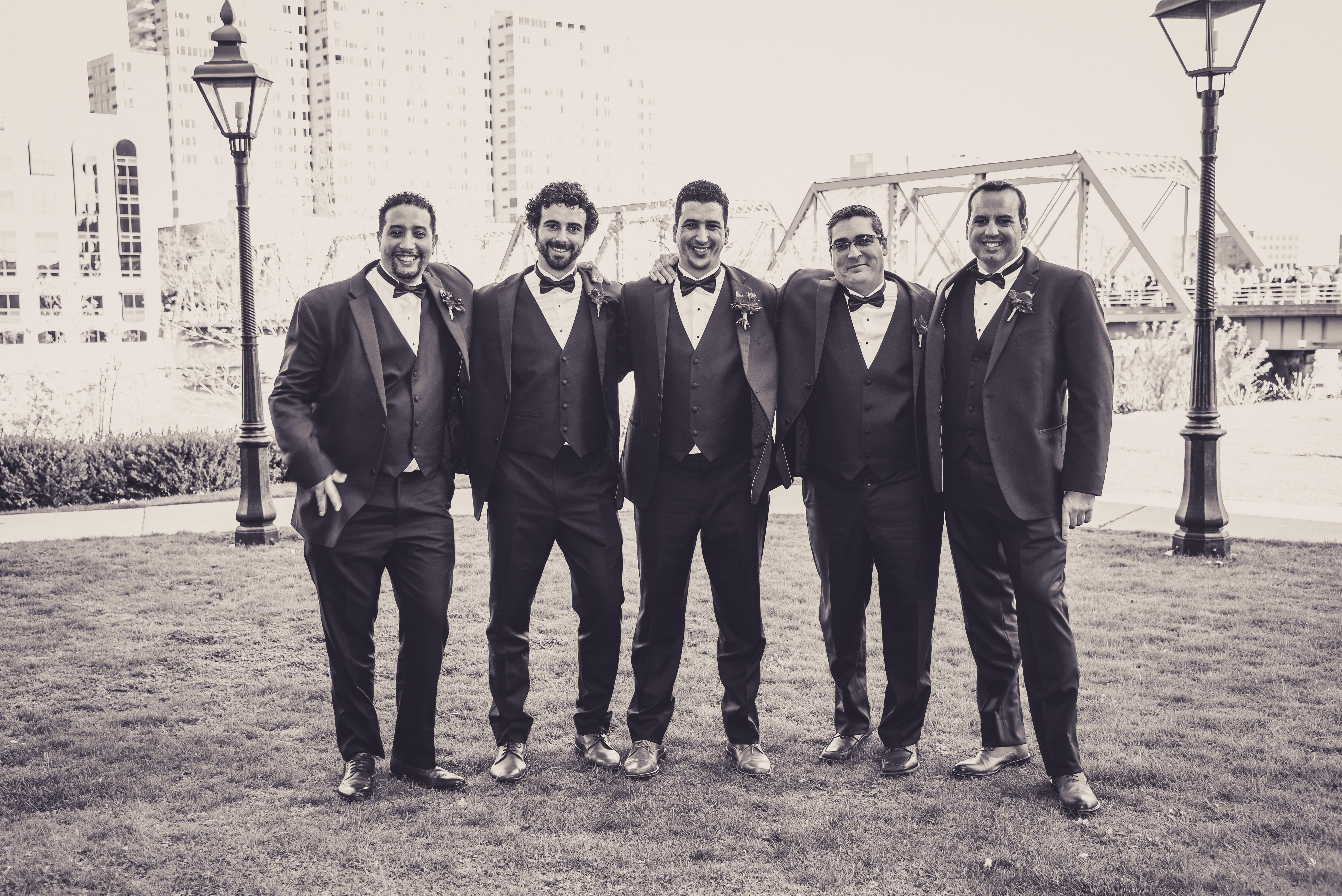 groomsmen in front of a bridge