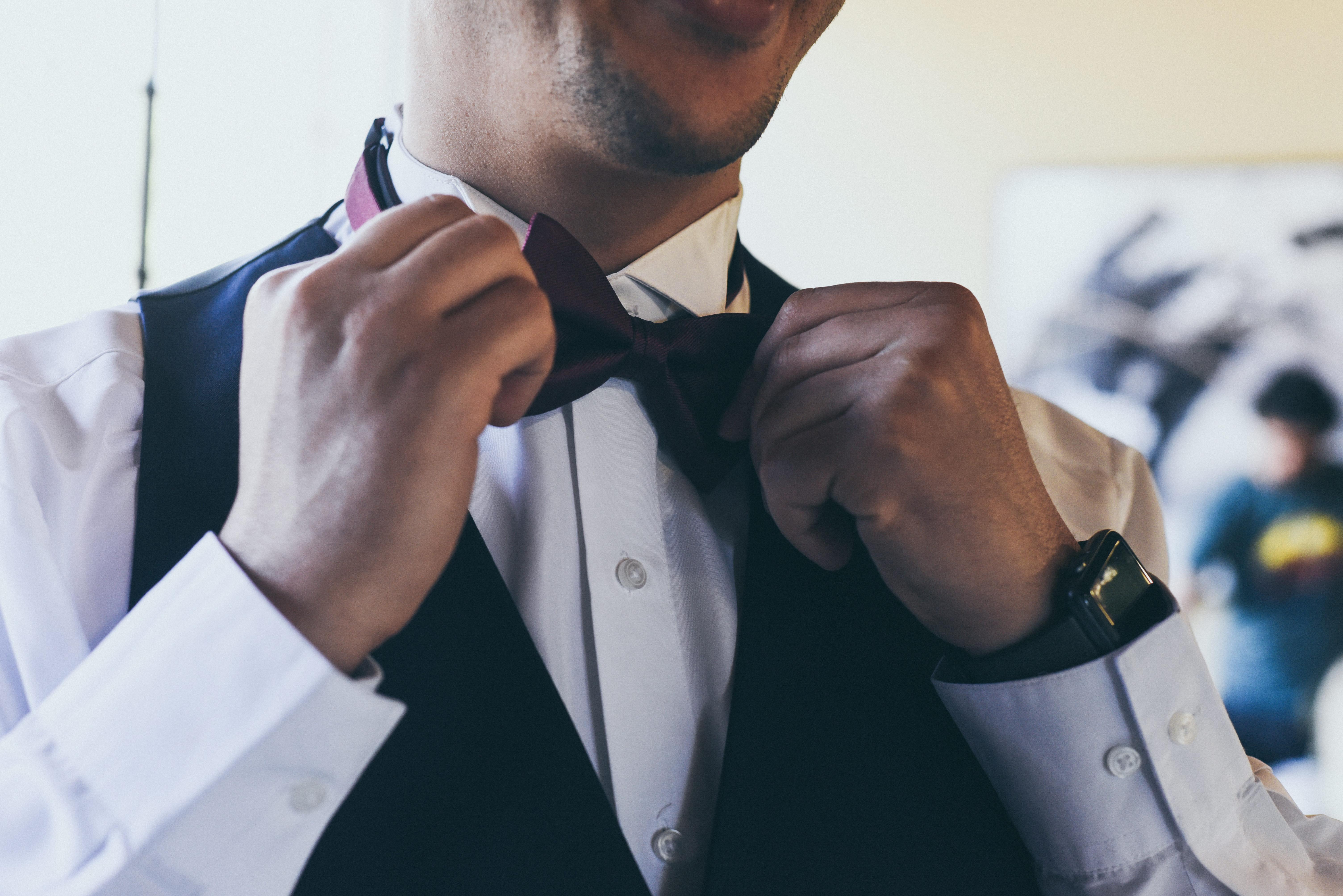 close up image of groom adjusting his tie