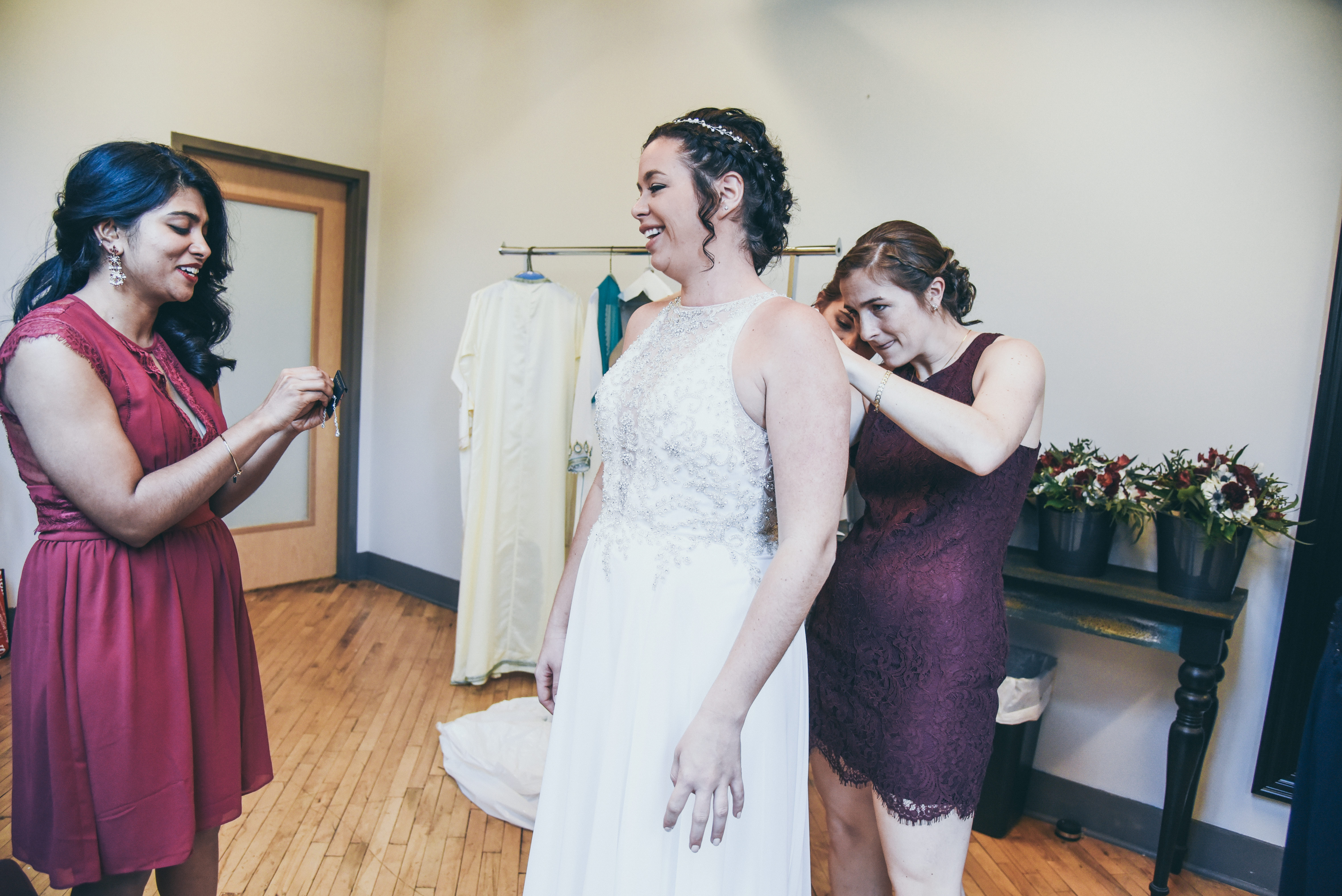 image of bridesmaid helping to fasten brides wedding gown