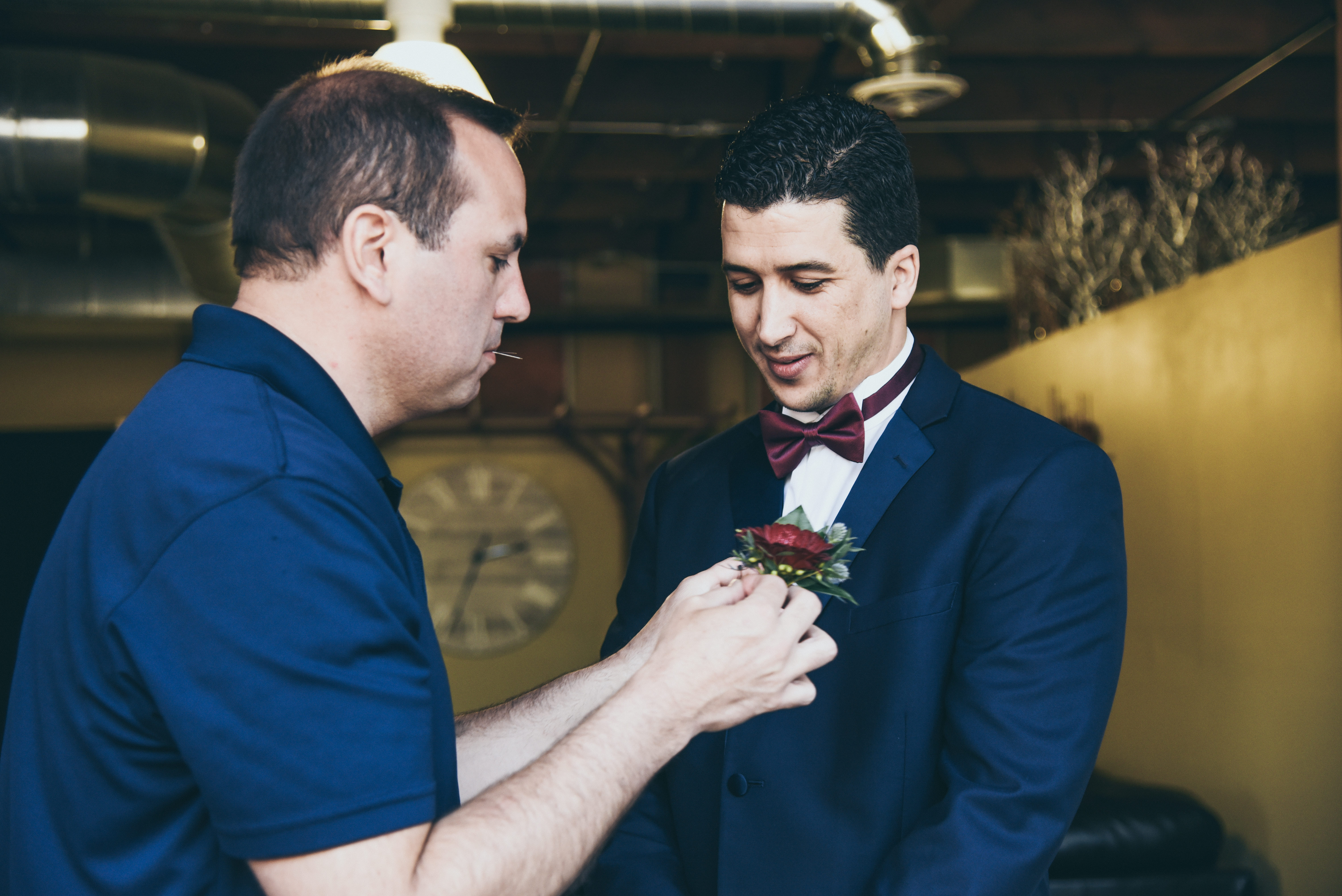 groom in a navy tux having his flower pinned on