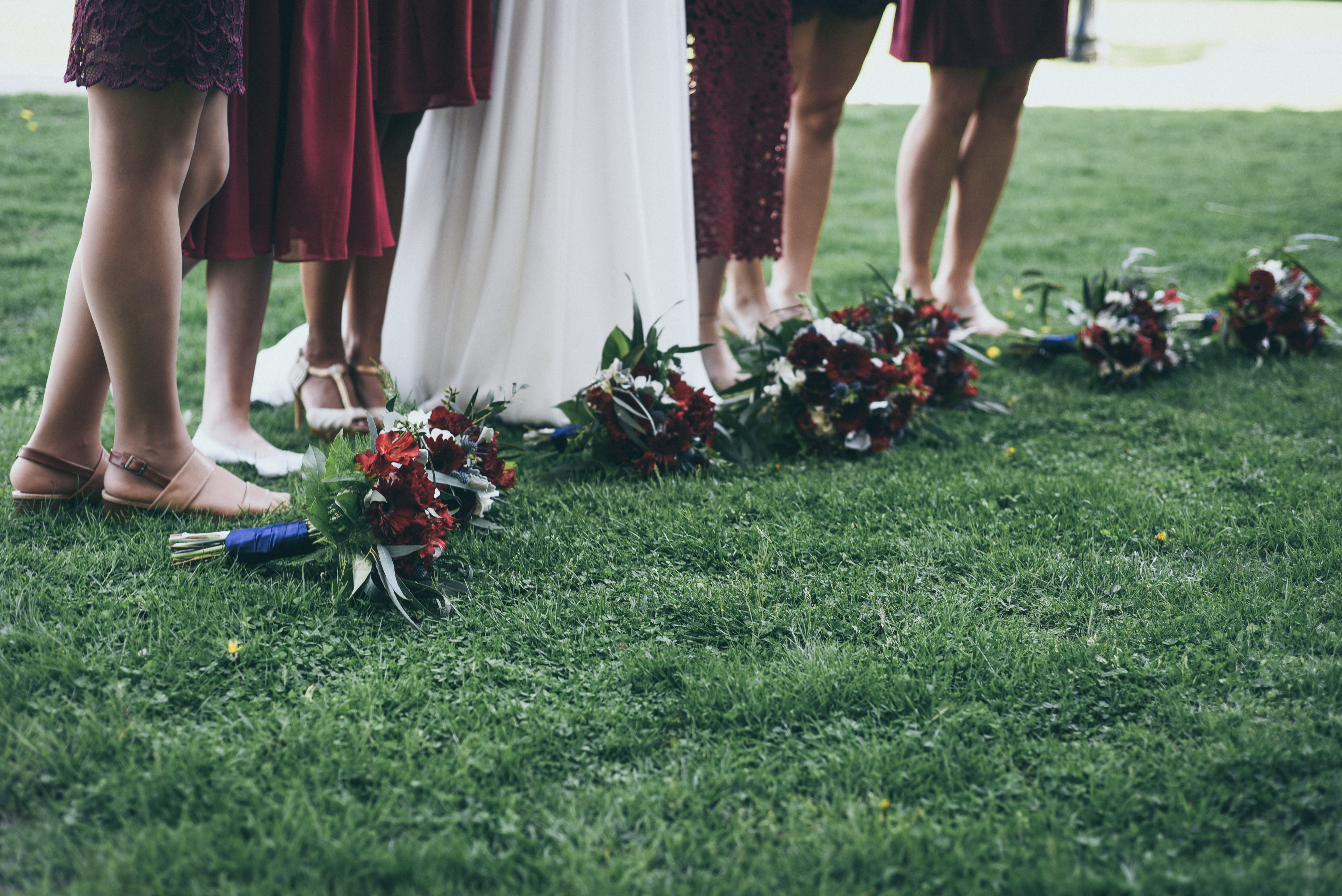 bridesmaids with bouquets at their feet
