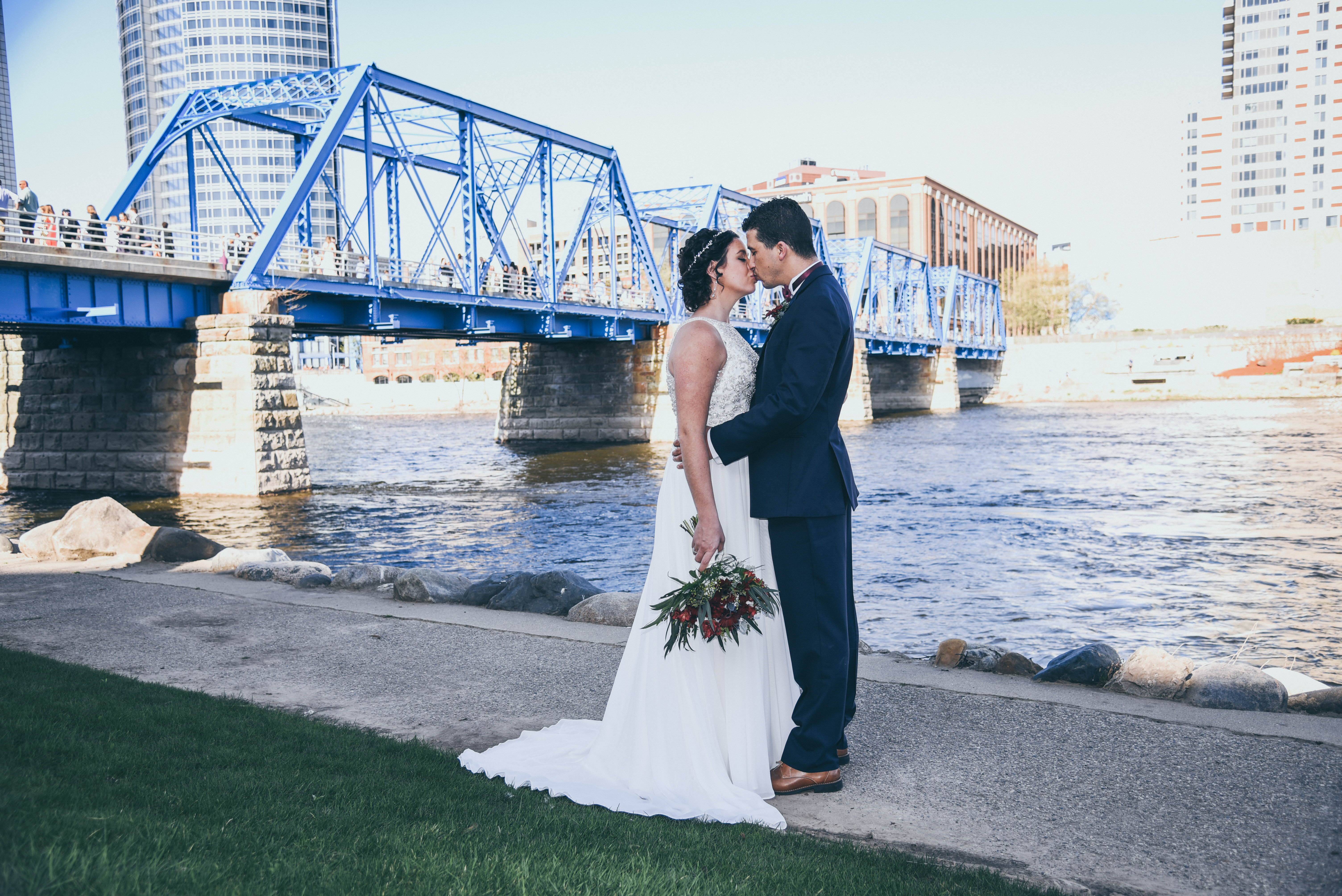 bride and groom kissing in front of a blue bridge
