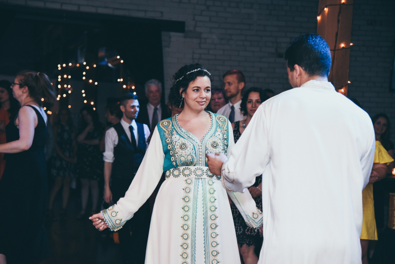 bride and groom putting on moroccan clothing at their reception