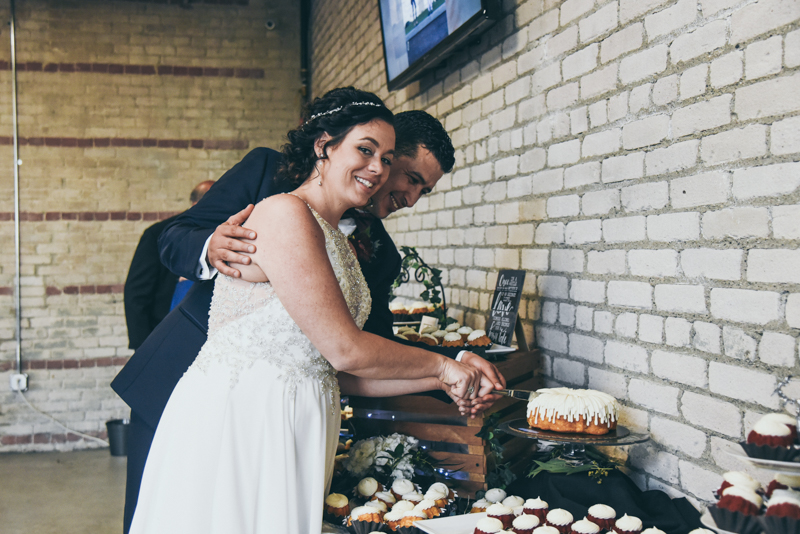 bride and groom cutting a bundt cake at a reception