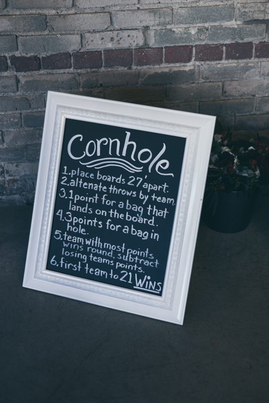 sign for cornhole boards at a wedding reception