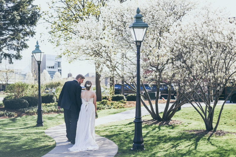 bride and groom walking under blossoming cherry trees